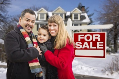 Tips For Buying a Home In The Winter - Picture of a warmly dressed family in front of home for sale real estate sign in the winter.